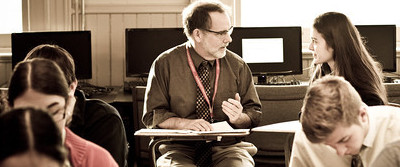 Upper school teacher, Randy Gehman, helps student in class.