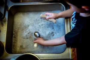 Child learns responsibility by helping to wash dishes.