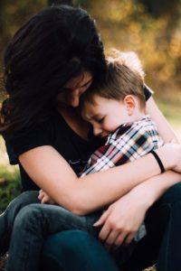 A vigilant mother hugs her child.