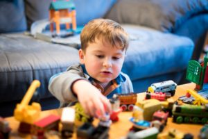 A child plays with wooden toy trains.