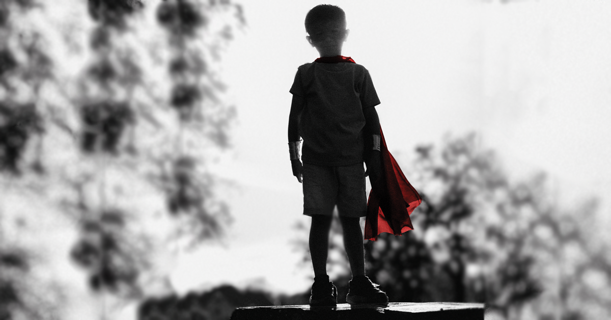 Boy in cape and mask pretends to be a hero.