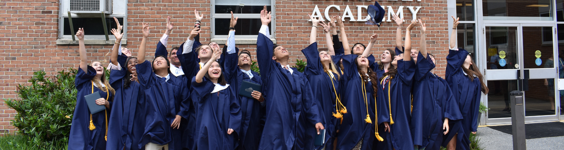 Dayspring graduates toss their hats outside to celebrate their graduation day.