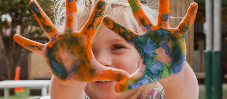A child raises his hands covered in swirled paint.