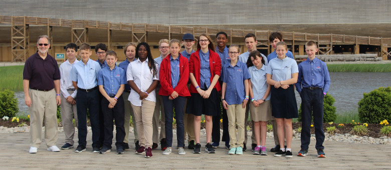 Dayspring 7th grade students stand with their teacher in front of the Ark Encounter.