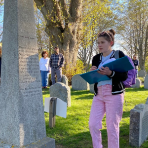 A young lady stands at William Bradford's tomb in Plymouth, Massachusetts.