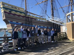 High school students stand in front of the Mayflower II in Plymouth, Massachusetts
